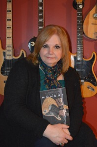 Picture of Karen Cimms, author holding her book, At This Moment